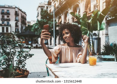 A cute young biracial female with a curly Afro hair is sitting at a wooden table of an outdoor cafeteria with a glass of orange fresh juice in front of her and taking selfie using the smartphone