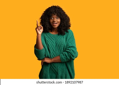 Cute young black woman in green outfit pointing finger up on yellow studio background, having great idea, copy space. Inspired african american lady with curly hair found solution
