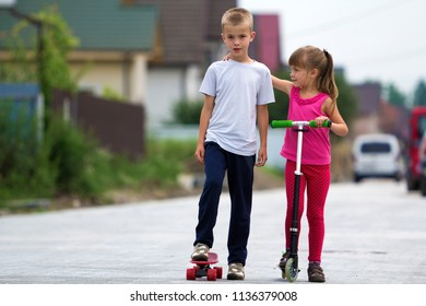 Cute young blond children, brother and sister, girl in pink clothing on scooter and handsome boy on skateboard playing together on sunny street blurred background. Children games and fun concept.