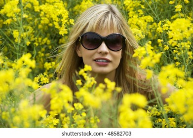 cute young blond woman outdoor in a yellow field wearing sun glasses and a yellow shirt
