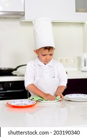 Cute young boy in a chefs toque and white apron standing at a counter in the kitchen carefully checking his dinner plates for cleanliness before serving the meal