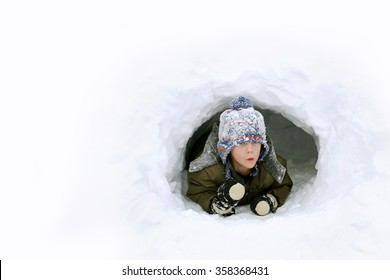 A cute young boy child is playing outside in a igloo fort tunnel he dug in a pile of snow on a winter day.