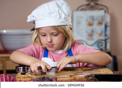 A cute young boy is concentrating while he is baking gingerbread cookies