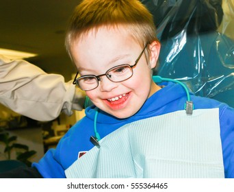 Cute Young Boy With Downs-Syndrome Sitting in Dentist Chair