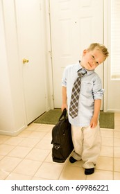 A cute young boy is dressed as a businessman, and stands by the door, carrying a briefcase