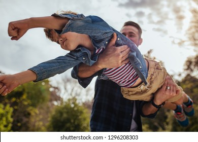 Cute young boy flying in hands of his dad. Small kid playing with his father at the park.