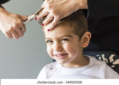 Cute Young Boy Getting A Haircut At Home