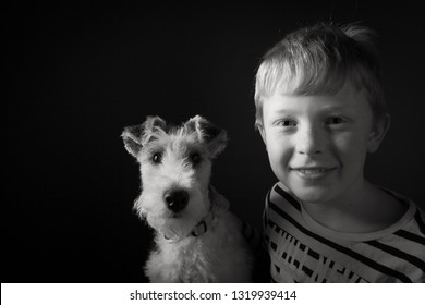 Cute young boy and his 1 year old wire fox terrier in the studio against a black background in monochrome