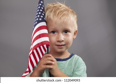 A cute young boy holds an American flag next to his head.