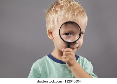 A cute young boy holds a magnifying glass up to his eye.