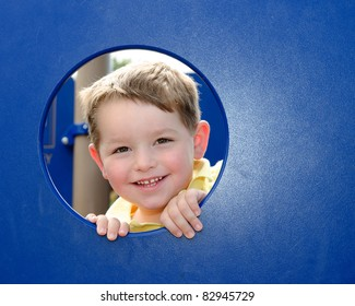 Cute young boy kid or child peeks through hole at playground outdoors at park.