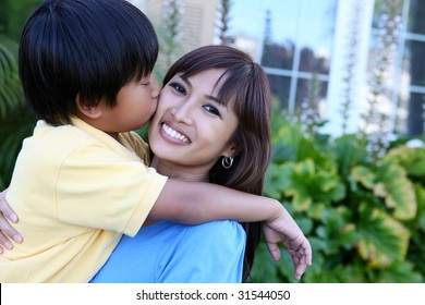 A cute young boy kissing his mother outside home