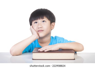 Cute young boy learning and thinking on the table.