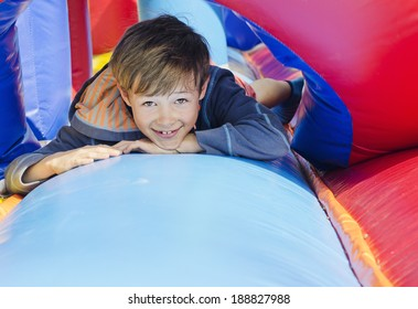 Cute young boy lying down on a bouncy castle