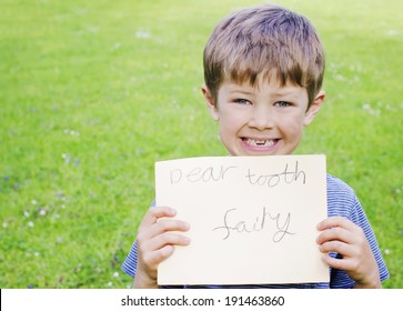 Cute young boy with a missing tooth holding a sign for the tooth fairy