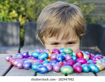 Cute young boy peering over a table looking at a big pile of chocolate Easter eggs