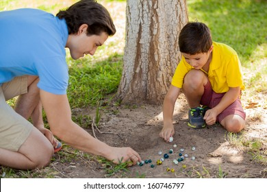 Cute young boy playing with marbles outdoor with his father