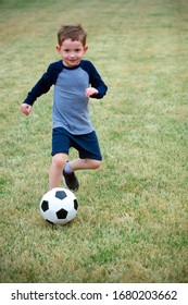cute young boy playing soccer in back yard