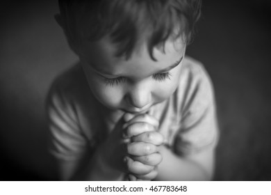 A cute young boy praying with hands clasped, in black and white.