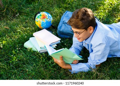 cute, young boy in round glasses and blue shirt reads book lying on the grass in the park. Education, back to school concept
