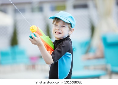 Cute young boy shooting water gun outdoors
