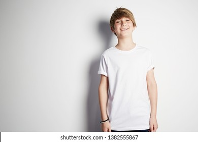 Cute young boy in white T-shirt posing in front of white empty wall. Portrait of fashionable male child. Smiling boy posing, blank wall on background. Concept of children style and fashion