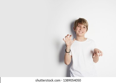 Cute young boy in white T-shirt posing like tiger in front of white empty wall. Portrait of fashionable male child. Concept of children style and fashion. Mock-up