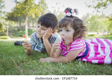 Cute Young Brother and Baby Sister Enjoying Their Lollipops Outdoors on the Grass.
