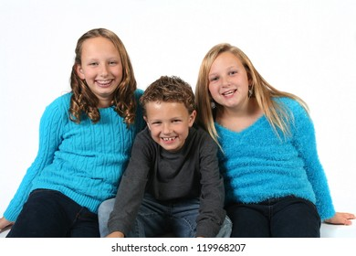 Cute young brother with older sisters isolated on white background