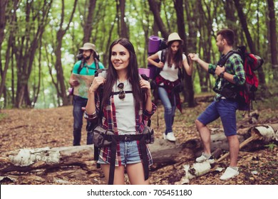 Cute young brunette is amazed by the beauty of forest, the guy is holding lady`s hand, helping during hiking. Four cheerful tourists