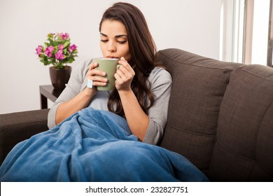 Cute young brunette covered in a blanket on a cold day enjoying a cup of tea
