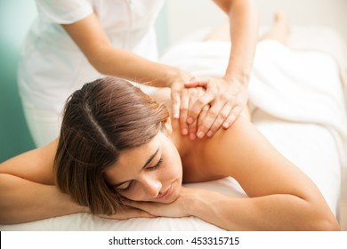 Cute young brunette getting a very relaxing massage from a therapist at a health clinic