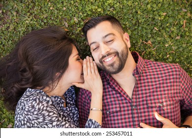 Cute young brunette whispering some words to her boyfriend's ear while relaxing at a park