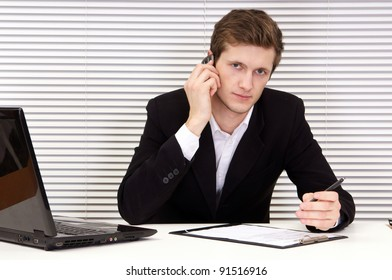 cute young businessman sitting at table in office