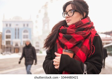Cute young caucasian brunette woman student on a walk in europe city streets. She wearing blac coat and plaid red scarf. Cold winter weather. Woman drinks coffee from a to-go cup