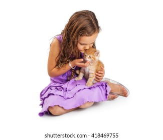 Cute young caucasian girl with long hair kissing a little kitten on head. Isolated on white.