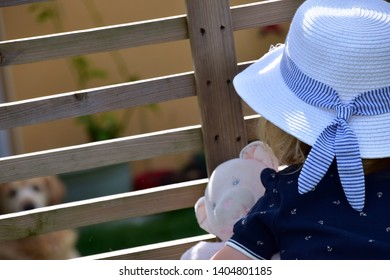 Cute young caucasian little girl dressed with a white hat with a blue ribbon and a blue dress holding a pink teddy bear. She's standing against the backyard gence, staring at a dog on the other side.