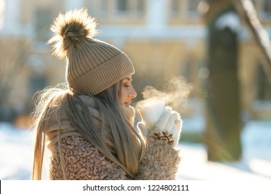 Cute young Caucasian teenage woman in beige fur coat, hat with pompon, scarf and white mittens holding steaming white cup of hot tea or coffee, outdoor in sunny winter day. Bask in the cold