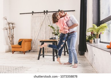 Cute young couple dancing at home.