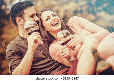 Cute young couple drinking red wine on a picnic in park.