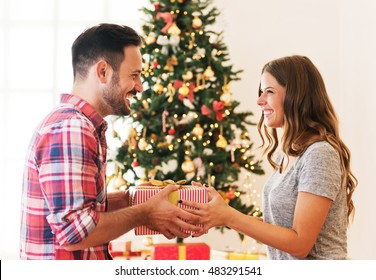 Cute, young couple exchanging Christmas presents on Christmas morning