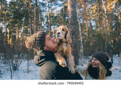 Cute young couple having fun in winter park with their dog golden retriever on a sunny day and smiling. Woman and man hugging with dog in winter snowy countryside