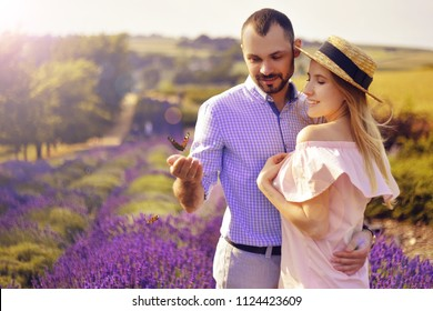 Cute young couple in love in a field of lavender flowers. Enjoy a moment of happiness and love in a lavender field. A pair of lovers holding a butterfly. Butterflies in the stomach. Love.