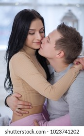 cute young couple in love hugging and kissing at home