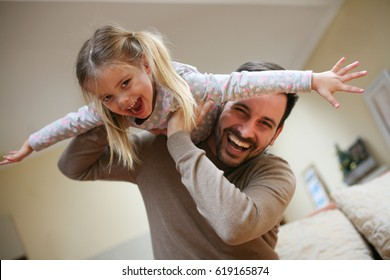 Cute young daughter on a piggy back ride with her dad. Looking at camera.