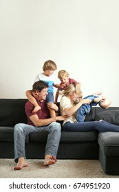 Cute Young family plays around on couch at home