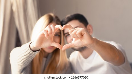 Cute young family of two making heart with their fingers at home, focus on hands