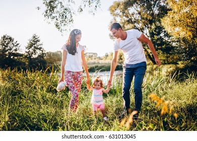 Cute young family walking through the meadow on a sunny day