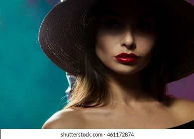 Cute young fashion model in hat with wide brim posing in studio on multicolor background