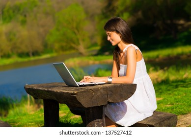 Cute young female with a laptop sitting on the brench